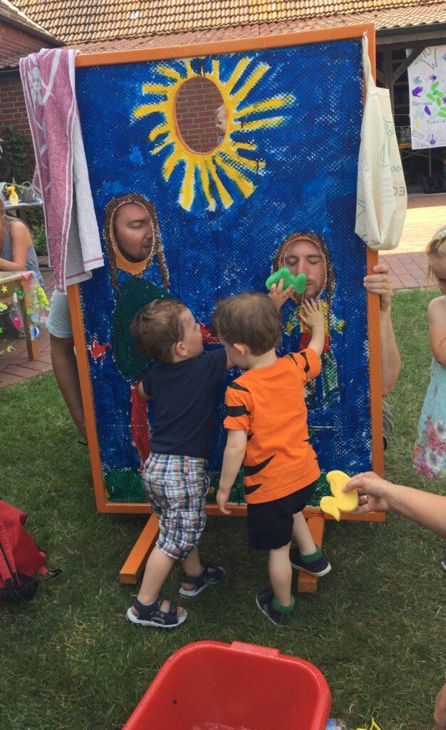 Spiel und Spaß der Kinder an der Fotowand mit ihren Eltern